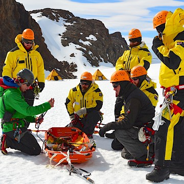 A group of people in yellow listening to instructions with search and rescue equipment.