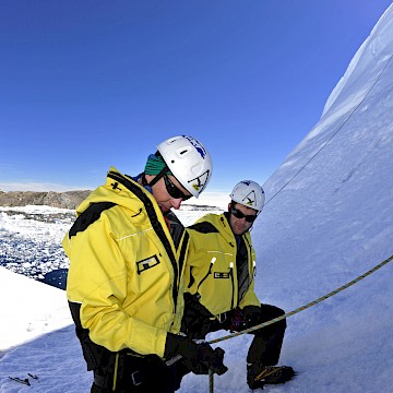 Two people in yellow examining ropes at the base of an ice cliff.