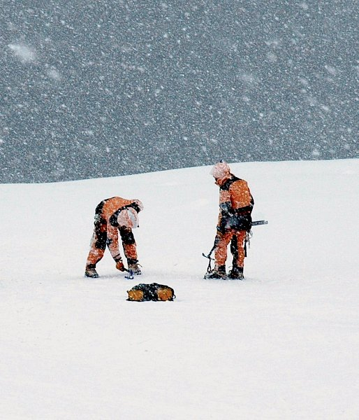 Six people in snowy weather adjusting ropes and rescue equipment.