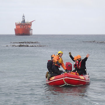 Expeditioners in small boat waving as they drive towards shore. Ship in background on a grey cloudy day.