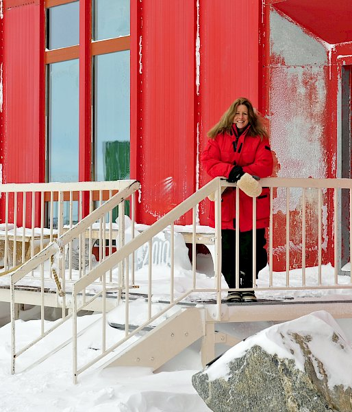 Station leader in red coat standing on snowy balcony with red building in background.