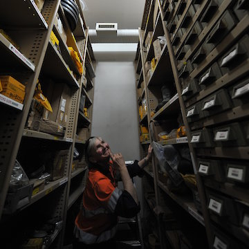 Woman looking up at banks of small drawers in a warehouse.