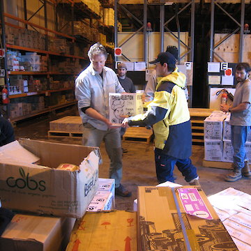 Two people carrying a box in the warehouse.