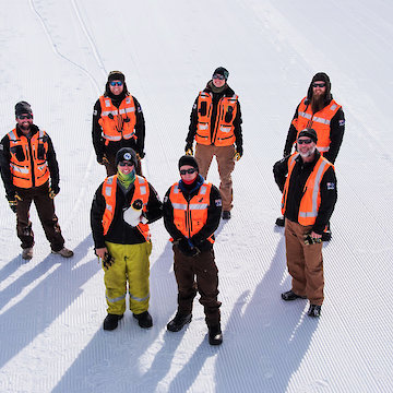 Group of six expeditioners in high visibility vests standing on ice.