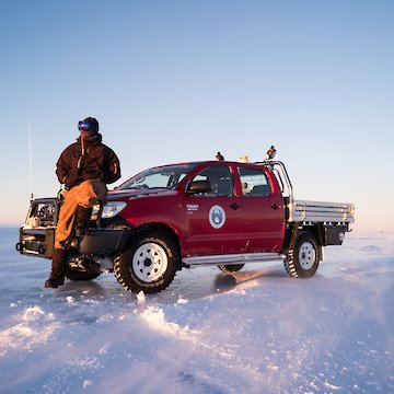 Person sitting on bonnet of red ute on ice.