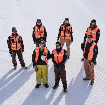 Group of expeditioners in high visibility vests standing on ice.