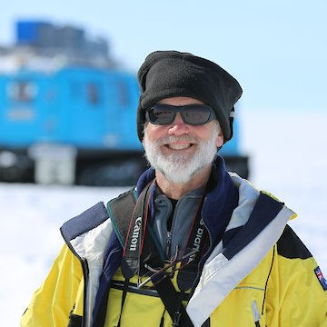 Man in sunglasses with blue over-snow vehicle in background.