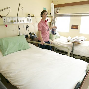 Woman standing beside beds in hospital facility.