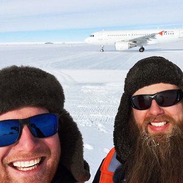 Two bearded men posing with plane on runway.