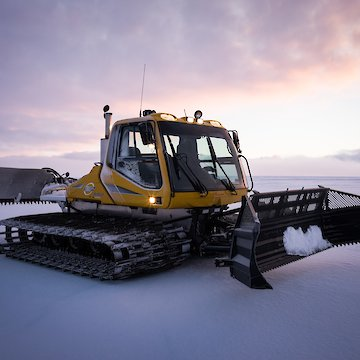 Large snow grooming vehicle.