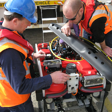 Two people examining remotely operated vehicle.