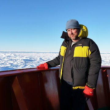 Man posing on ship with sea ice in background.