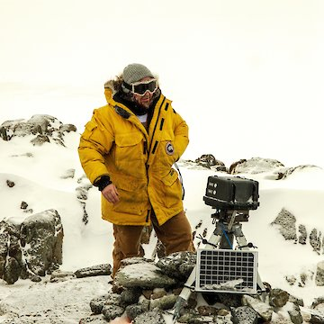 Person in yellow coat beside camera and solar panel.