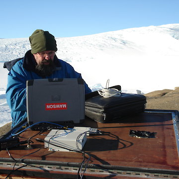 Man in beanie working on laptop outdoors in snowy landscape.