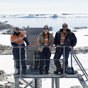 Three people standing on metal structure with ice and ocean in background.
