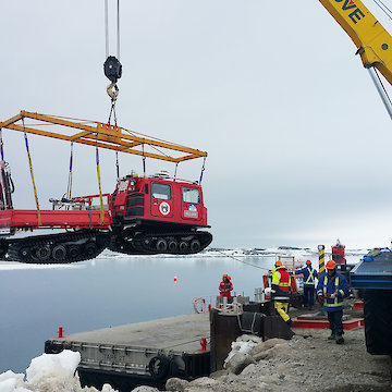 Crane lifting over-snow vehicle off barge at wharf.