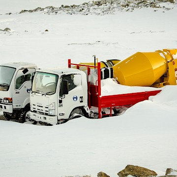 Two concrete mixer trucks half buried in snow.