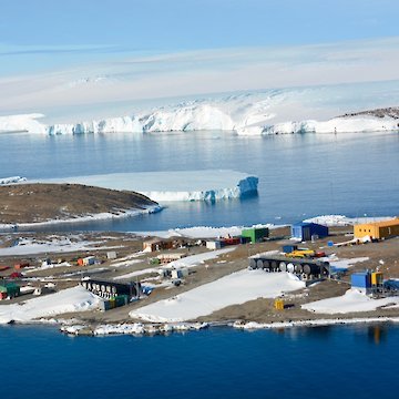 Aerial view of Mawson station with ice cliffs in background.