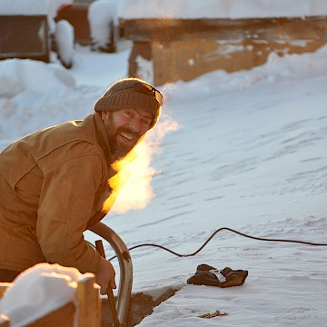 Bearded man using tools in snow.
