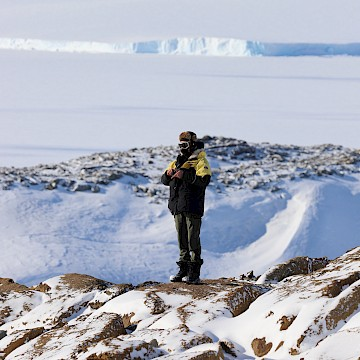 Person in rugged clothing with expansive ice sheet in background.