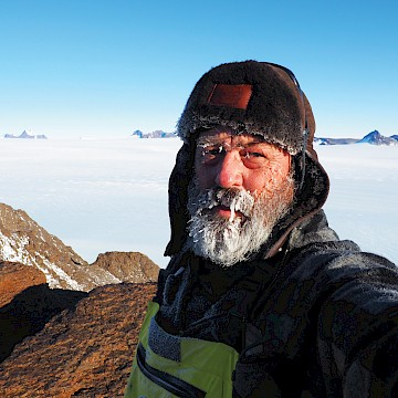 Man with icy beard taking selfie atop rocky mountain with ice sheet in background.