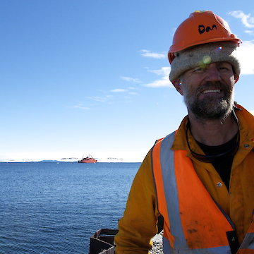 Portrait of man in hard hat with ship in background.