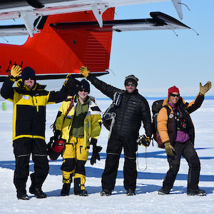 Four people waving at the camera while posing beside the tail of a small plane.